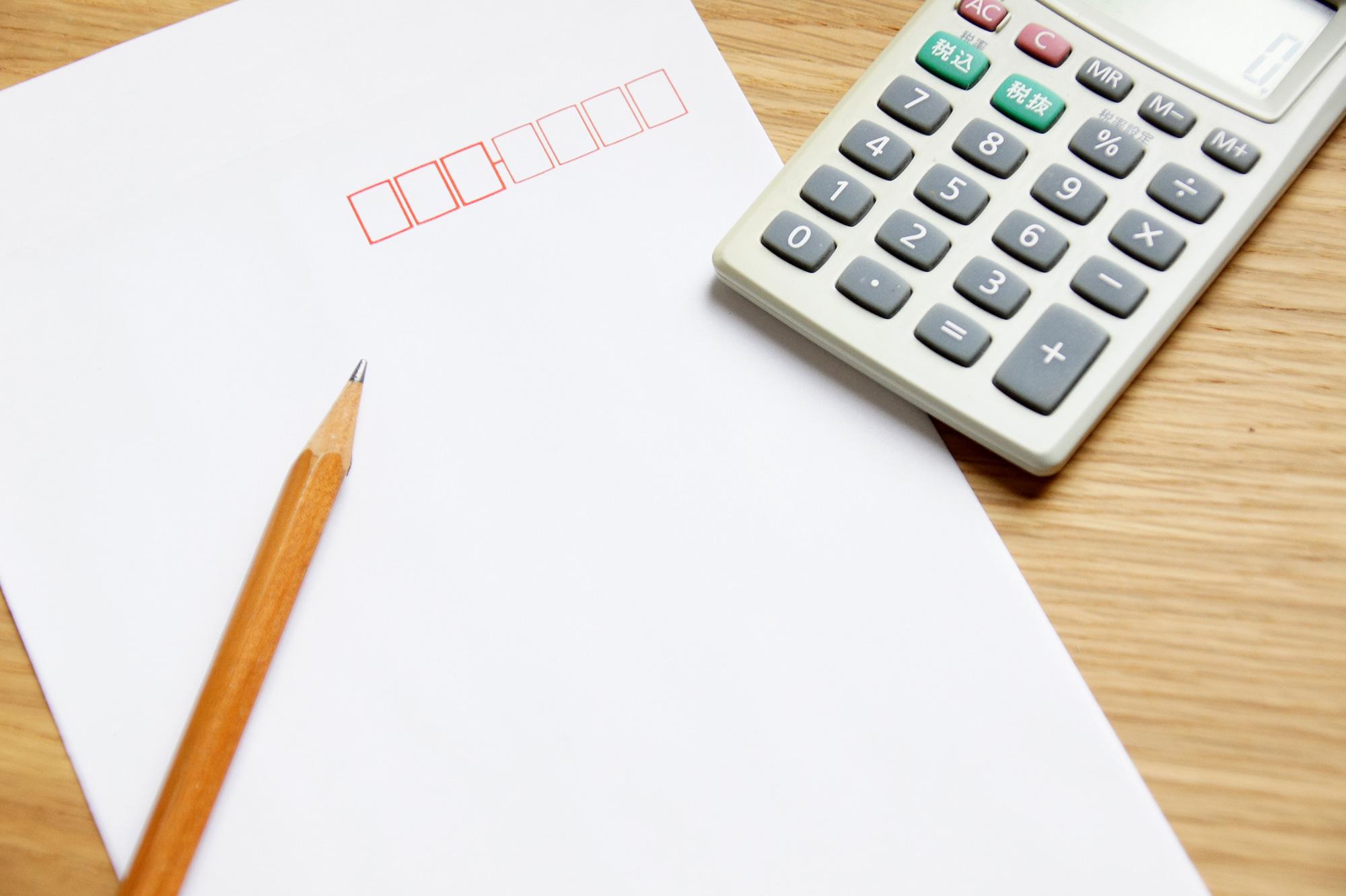 電卓と封筒と鉛筆の写真のフリー素材