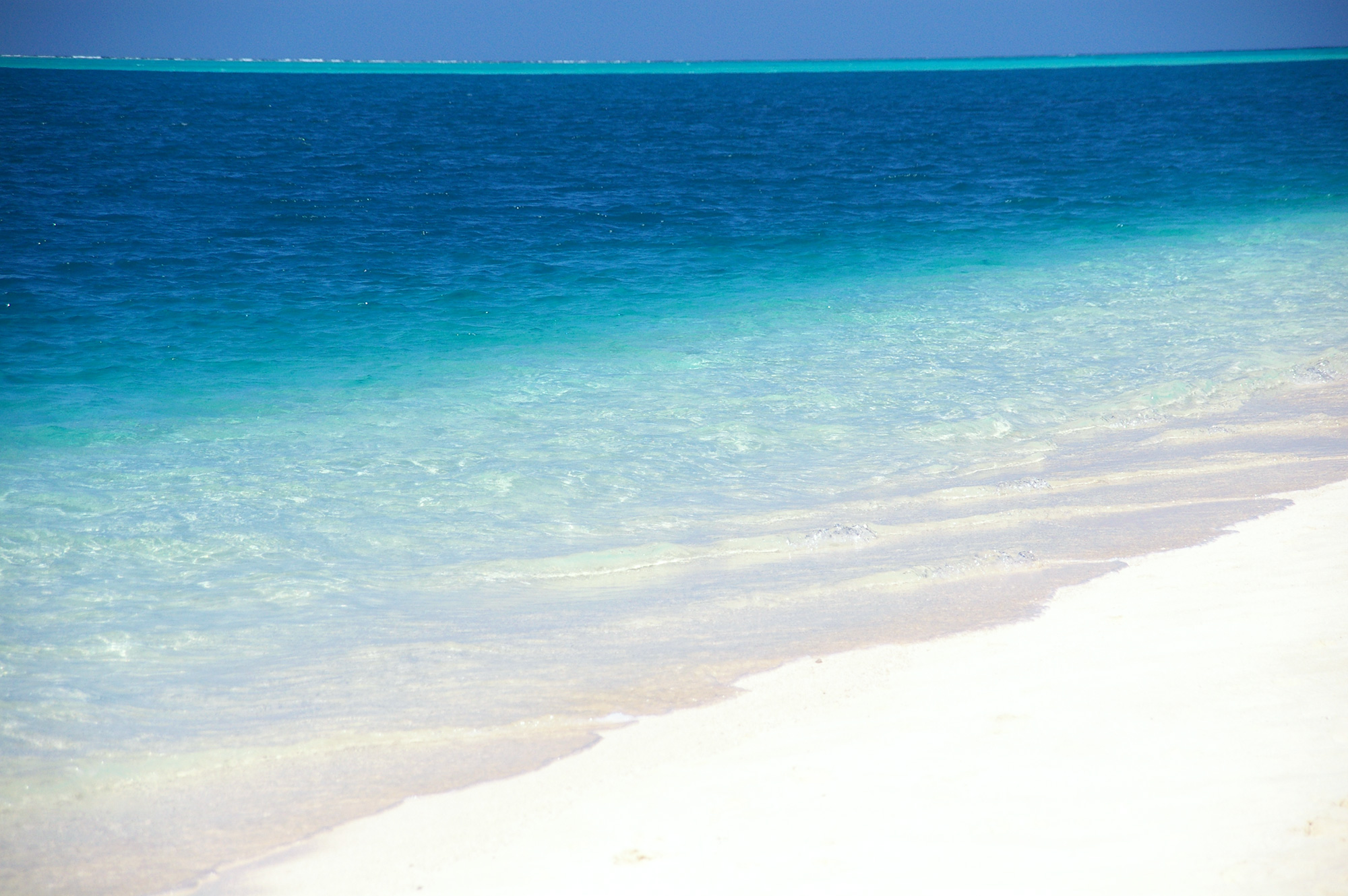 白い砂浜の波打ち際の写真のフリー素材
