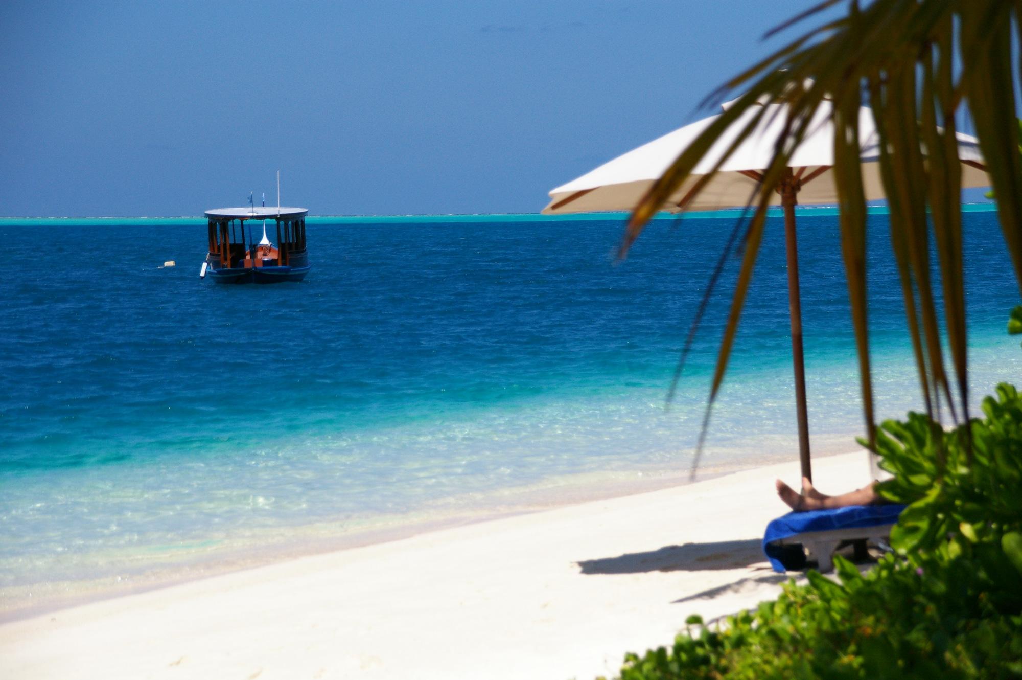 ビーチパラソルと小船のフリー写真素材