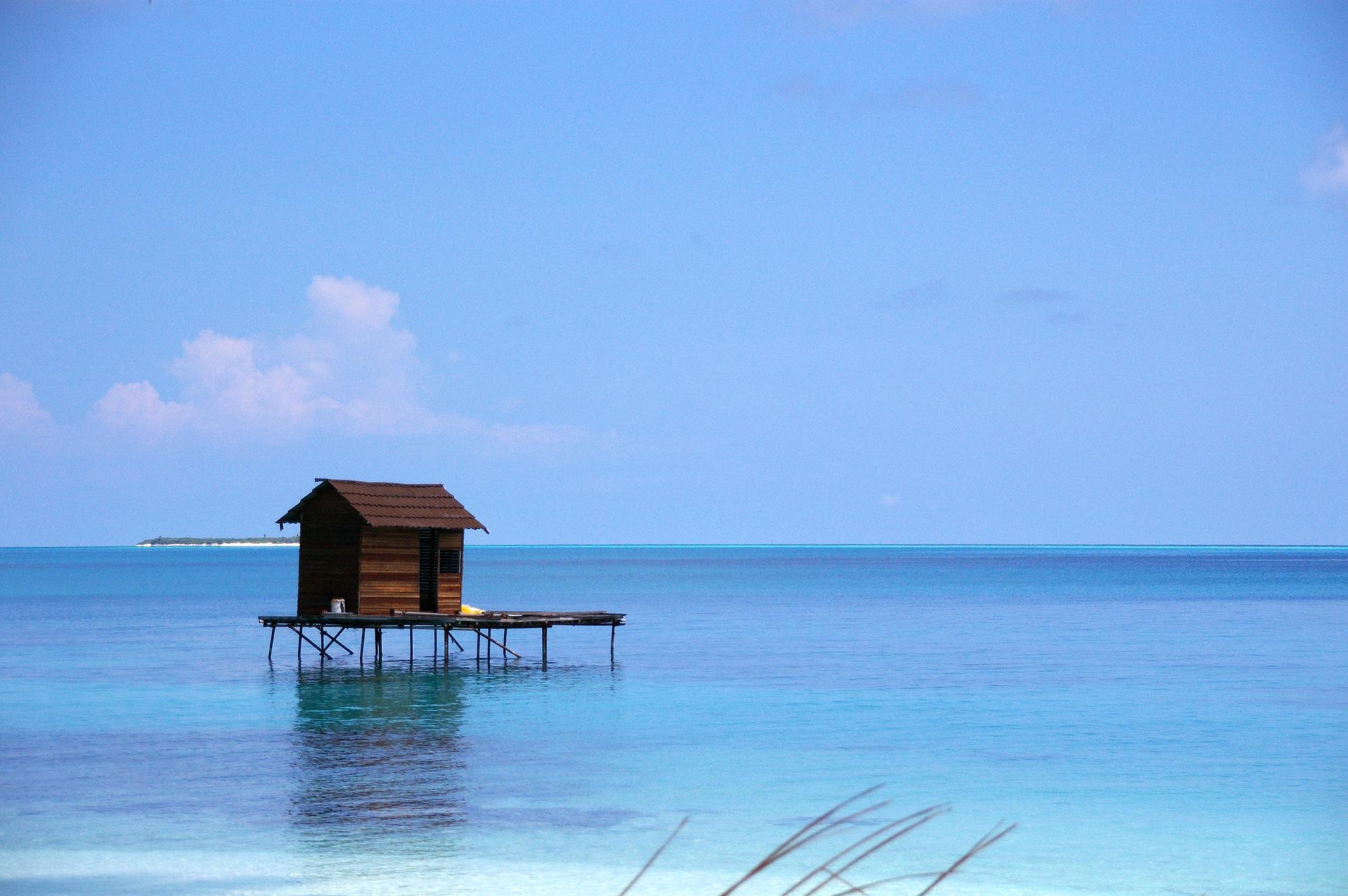 青い海に浮かぶ小屋のフリー写真素材